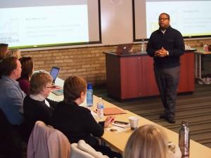 Milner standing in front of workshop participants