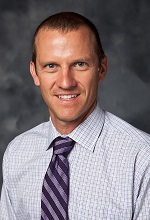 formal portrait image of Greg Rhodes in a dress shirt and tie, smiling