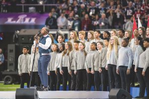 A youth choir performs behind singer Leslie Odom Jr. on the field of U.S. Bank Stadium during the 2018 Super Bowl in Minneapolis.