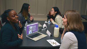 Latrisse White-Schneider (foreground - left) discusses her experience with Sarah Dohm, grad. program coordinator.