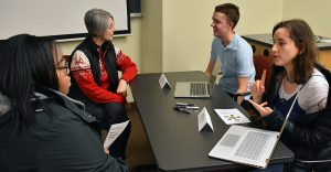 Tucker Alhstrom (back-right) shared his experience with Extension's 4-H Youth Development with Asst. Professor & Extension Specialist Joyce Serido while Brianna Brennan (foreground-right) discusses her work at the Sexual Violence Center with a guest.