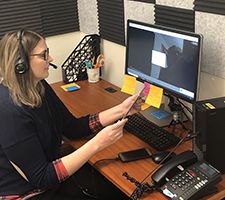 ICI's telehealth lab manager Jessica Simacek wearing a headset and looking at a tablet and a client on her computer screen.