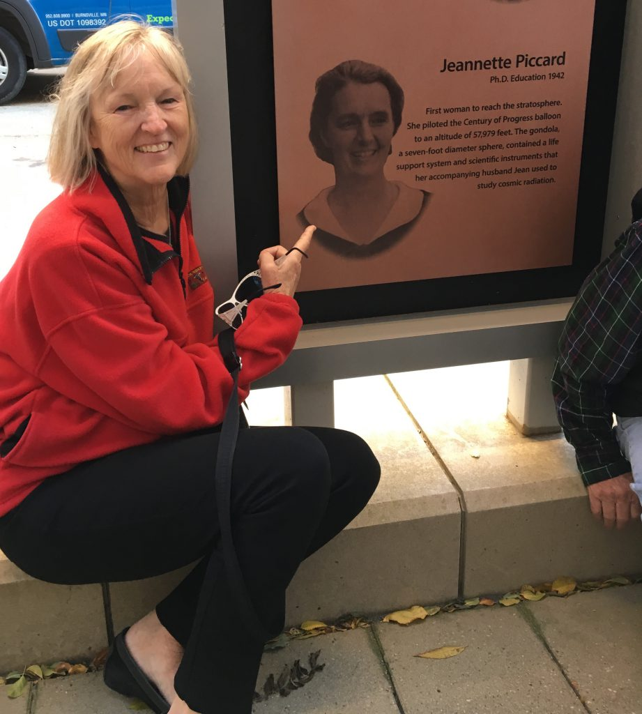 Color photo of Jane Piccard sitting on a ledge pointing to her grandmother's photo on a display panel