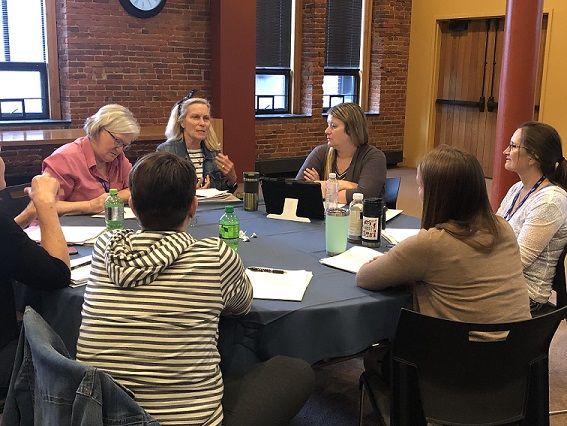 A group of session participants sits around a table talking about an exercise