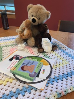 Three teddy bears, a newborn diaper and other materials for the session sit on a crocheted baby blanket