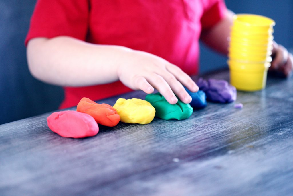A child plays with a row of multicolored lumps of clay