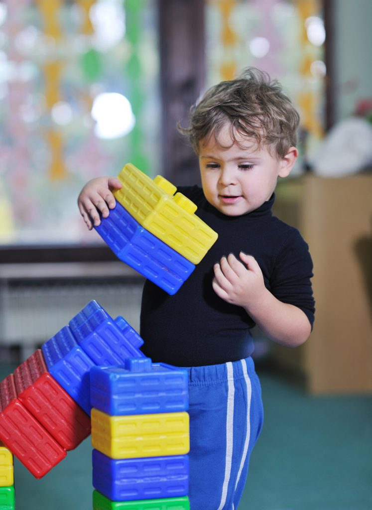A toddler boy builds a tower with big colorful plastic blocks.