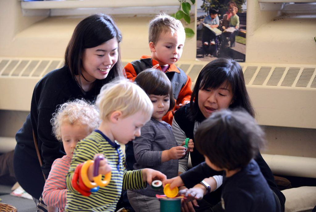 Two teachers and five students play together with toys