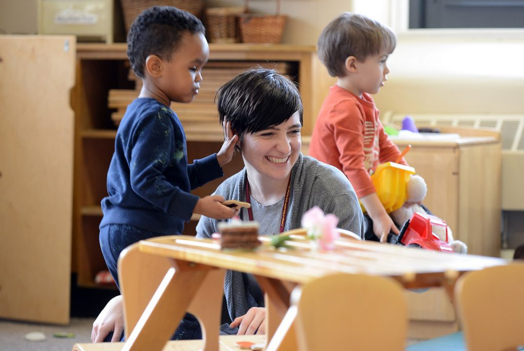 A young woman working in a daycare smiles as she interacts with toddlers and a boy touches her hair