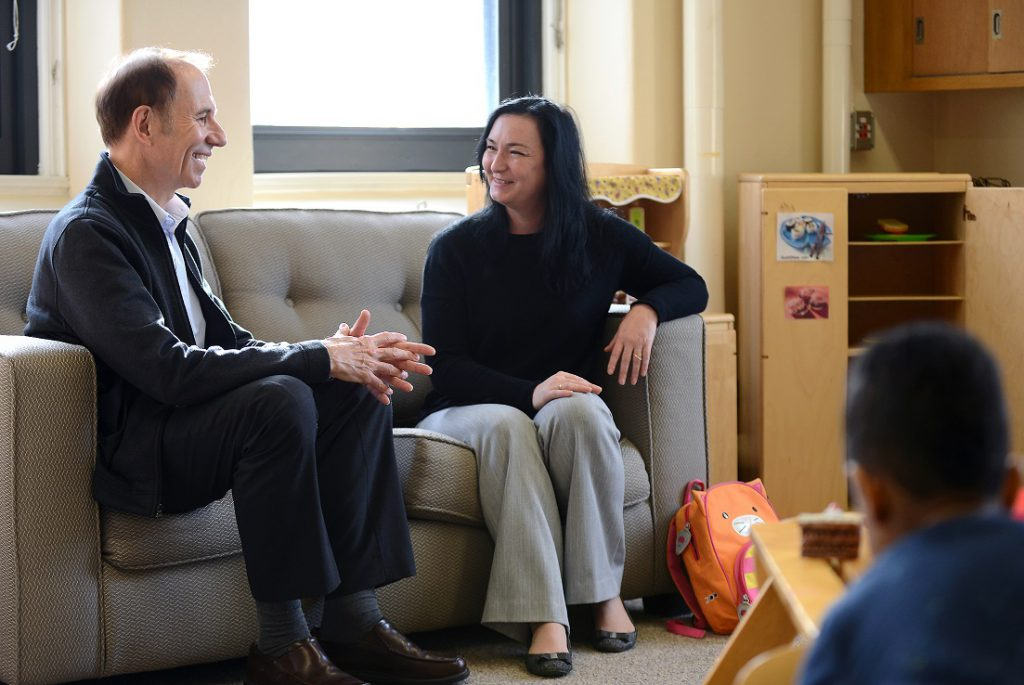 A man and a woman smile as they talk on a couch in a preschool classroom