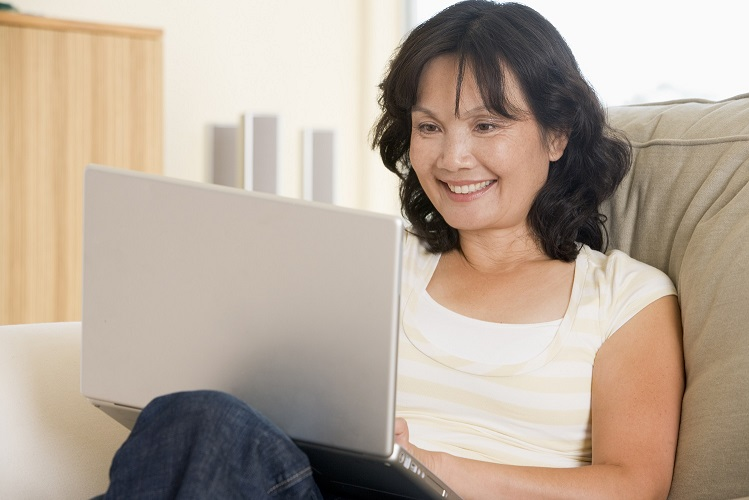 A woman smiles while using a laptop on her couch