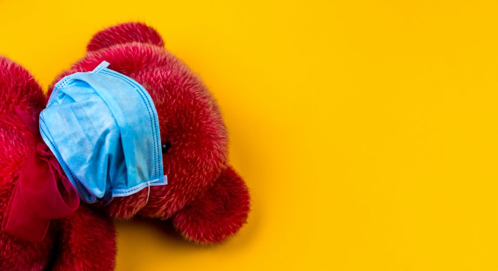 A red teddy bear lying on a yellow background with a face mask on