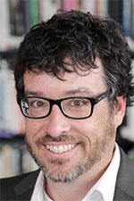 Portrait image of Dr. Doug Hartmann, slightly bearded and in black-rimmed glasses, smiling in gray blazer over a white dress shirt